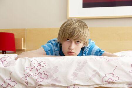 Teenage Boy In Bedroom Looking Sad photo