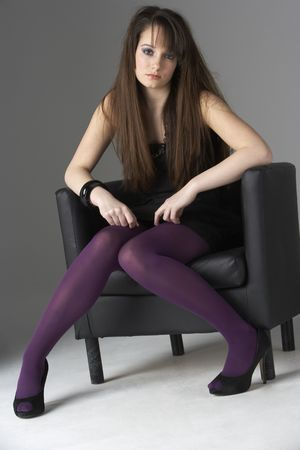 Studio Portrait Of Fashionably Dressed Teenage Girl Sitting In Chair photo