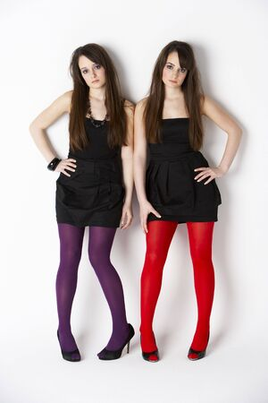 pre: Studio Portrait Of Fashionably Dressed Twin Teenage Girls Stock Photo