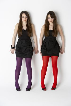Studio Portrait Of Fashionably Dressed Twin Teenage Girls photo