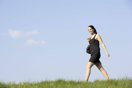 esc: Woman Walking Through Summer Countryside Stock Photo