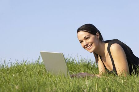 Woman Using Laptop Outdoors In Summer Countryside photo
