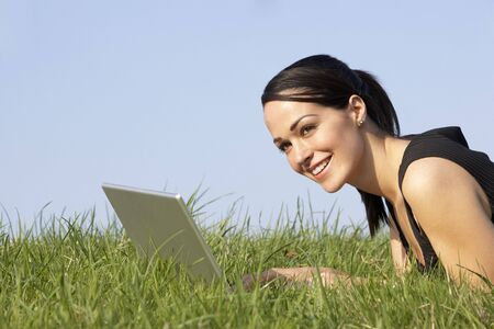 lady s: Woman Using Laptop Outdoors In Summer Countryside Stock Photo
