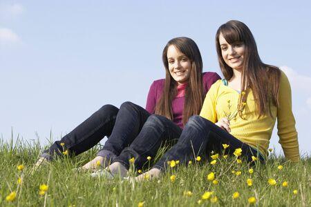 Twin Teenage Girls Sitting In Summer Meadow photo