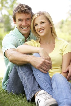 Portrait Of Young Couple Sitting In Park photo