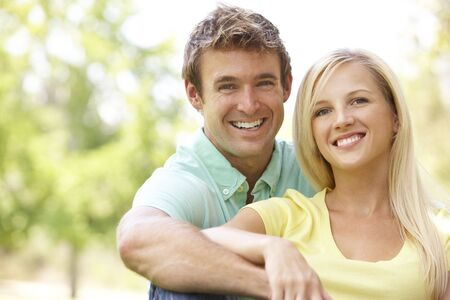 countryside loving: Portrait Of Young Couple Sitting In Park