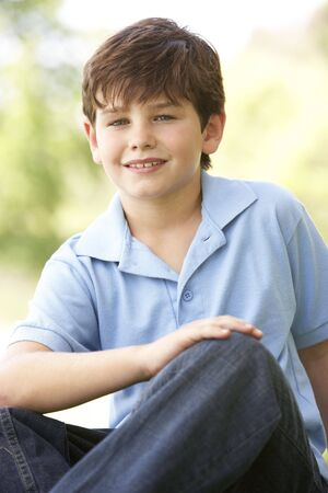 Portrait Of Young Boy Sitting In Park Stock Photo - 6135673