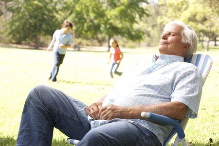 Senior Man Relaxing In Park With Grandchildren In Background photo