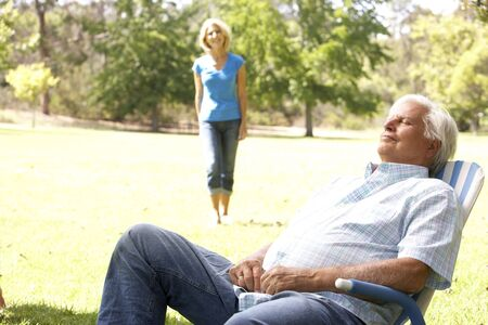 Senior Man Relaxing In Park With Wife In Background photo