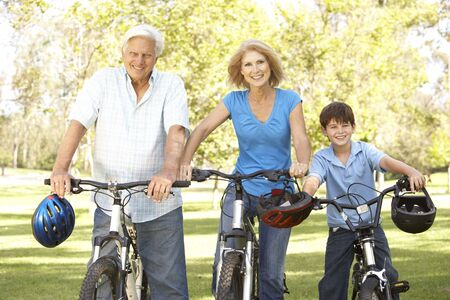 grandkids: Grandparents And Grandson On Cycle Ride In Park Stock Photo