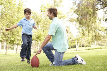dad and son: Father And Son Playing American Football Together
