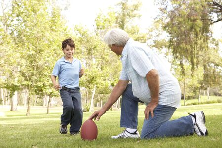 grandchild: Grandfather And Grandson Playing American Football Together