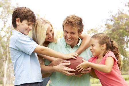 familia jugando: Familia jugando f�tbol americano juntos en el Parque
