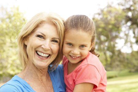 grandaughter: Grandaughter Hugging Grandmother In Park Stock Photo