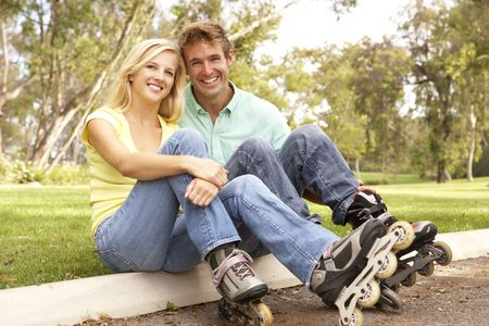 Couple Putting On In Line Skates In Park Stock Photo - 6143385