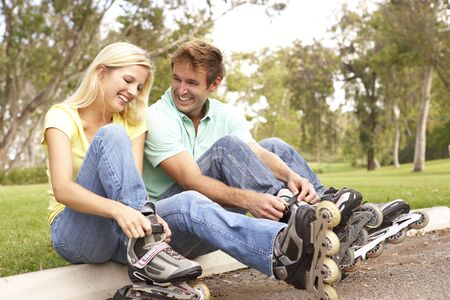 rollerblading: Couple Putting On In Line Skates In Park