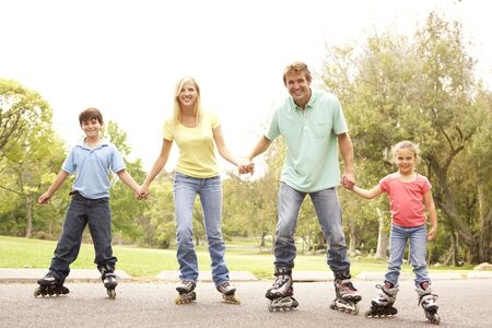 Familie dragen In lijn schaatsen In Park Stockfoto