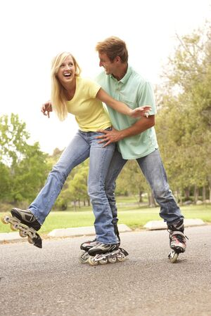 ve: Couple Wearing In Line Skates In Park Stock Photo