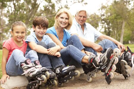 Grandparents And Grandchildren Putting On In Line Skates In Park photo