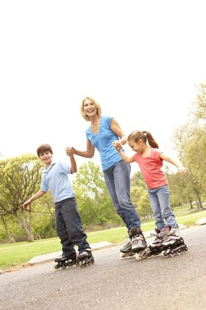 rollerblades: Grandmother And Grandchildren Skating In Park Stock Photo