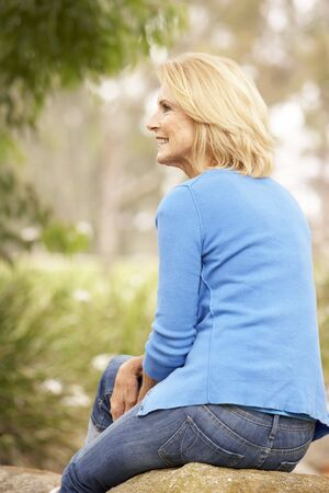Back View Of Senior Woman Sitting On Wall photo