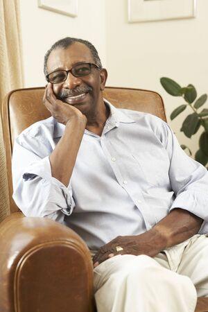 年配の男性人の自宅の椅子でリラックス 写真素材