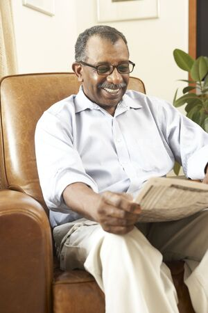 Senior Man Sitting In Armchair Reading Newspaper photo