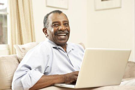 silver surfer: Senior Man Using Laptop At Home