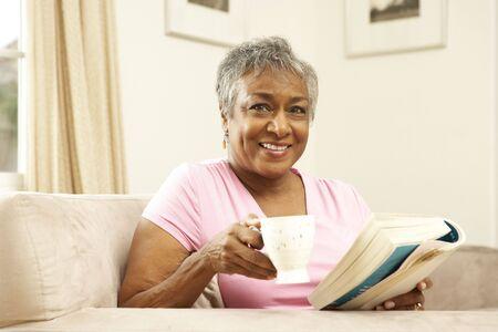 mujer leyendo libro: Libro de lectura de mujer senior con bebidas en el hogar