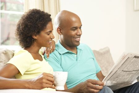 Couple Relaxing At Home With Newspaper photo