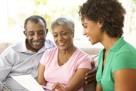 financial advisor: Senior Couple Talking To Financial Advisor At Home