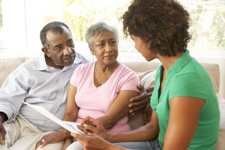 Senior Couple Talking To Financial Advisor At Home photo
