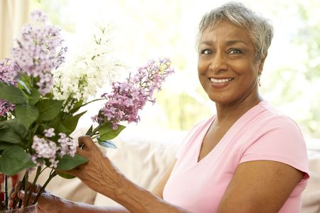 Senior Woman Flower Arranging At Home Imagens