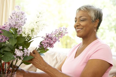 Senior Woman Flower Arranging At Home photo