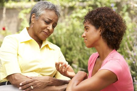 70s adult: Senior Woman Being Consoled By Adult Daughter