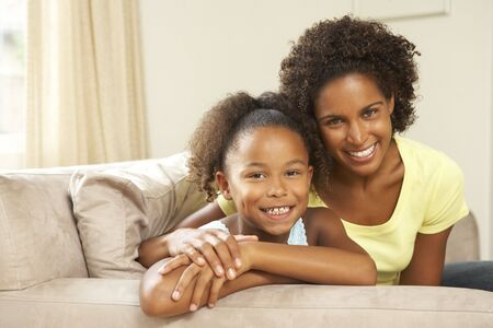 Mother And Daughter Relaxing On Sofa At Home Stock Photo - 6143251