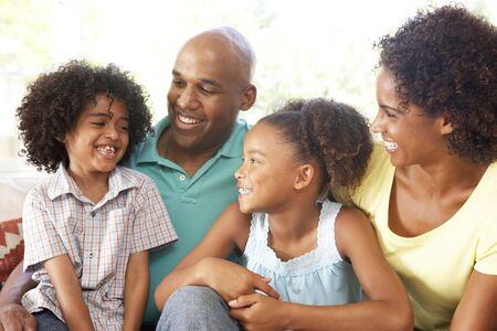 pere et fille: Jeune famille relaxant sur canap� � la maison