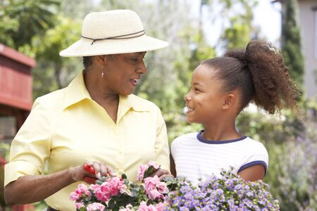 grand child: Grandmother With Granddaughter Gardening Together Stock Photo