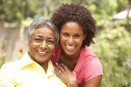 african american male: Senior Woman Hugging Adult Daughter Stock Photo