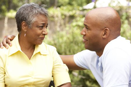30s adult: Senior Woman Being Consoled By Adult Son Stock Photo
