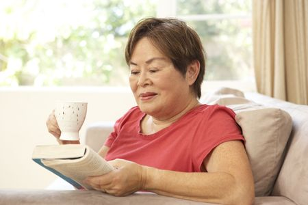Senior Woman Reading Book With Drink At Home photo