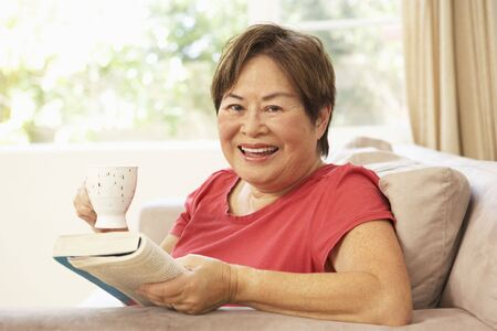 tea hot drink: Senior Woman Reading Book With Drink At Home