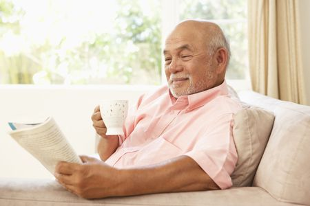 senior living: Senior Man Reading Book With Drink At Home