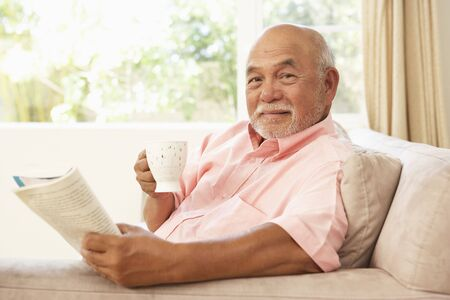 Senior Man Reading Book With Drink At Home photo