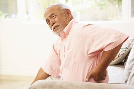 elderly pain: Senior Man Suffering From Back Pain At Home Stock Photo