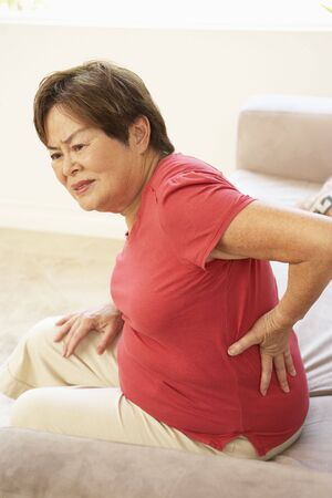 Senior Woman Suffering From Back Pain At Home photo