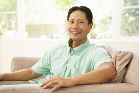asian home: Giovane uomo rilassante sul divano a casa