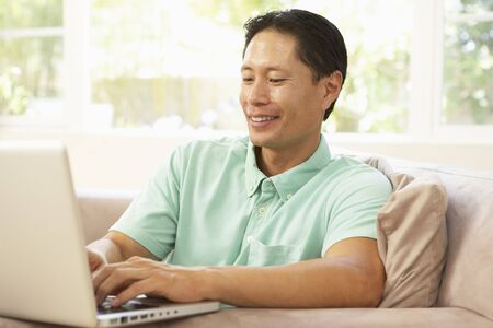 male age 40's: Young Man Using Laptop At Home