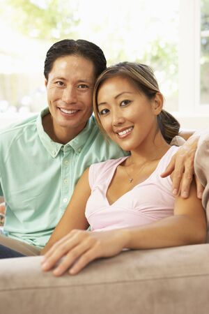 happy asian couple: Young Couple Relaxing On Sofa At Home