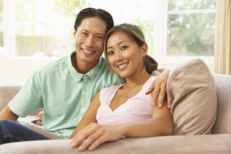 30s adult: Young Couple Relaxing On Sofa At Home